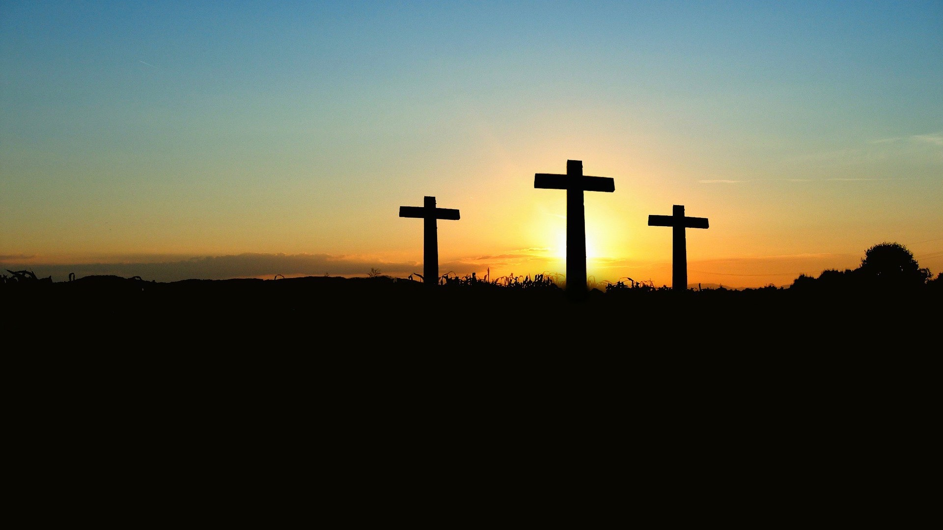 Three crosses in silhouette in front of a yellow sunset.
