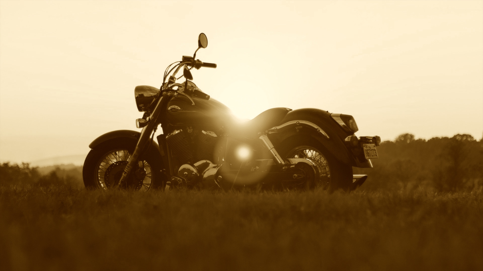Sepia picture of motorbike in front of sunset.